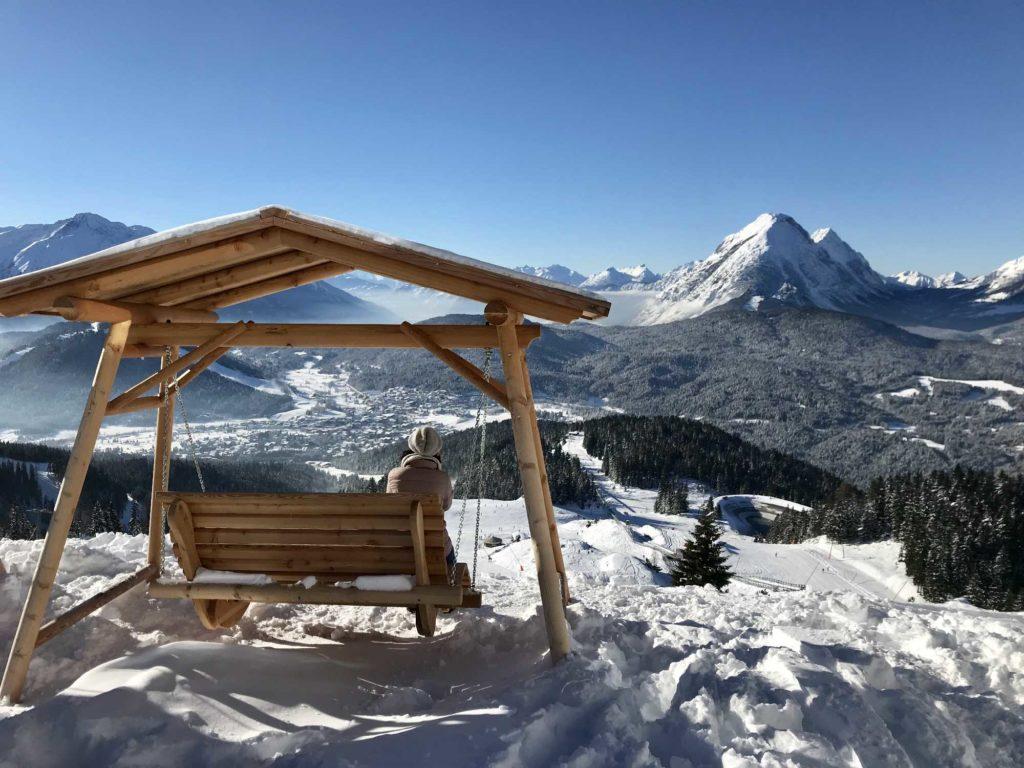 Die Schaukel steht im Schnee mit Blick auf die Berge. Markant ist die Spitze der hohen Munde.