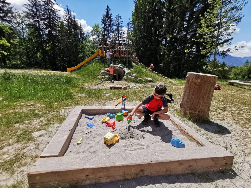 Das freie Gelände rund um die Tannenhütte mit Sandspielkasten, Rutsche, Kletterstämmen und Schaukel